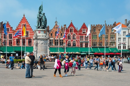 Bruges, Belgium - May 22, 2012: Citizens and guests of the city are walking near the old buildings and small cafes on Grote Markt, one of the main sightseeing places of Bruges in May 22, 2012. GPS information is in the file