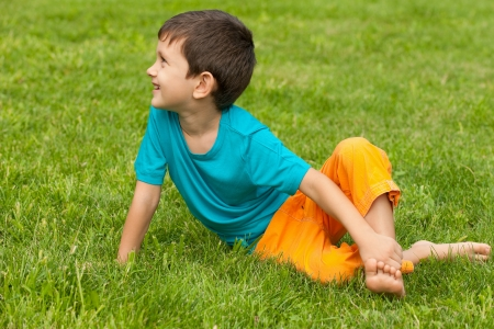 looking aside: A little boy in the blue shirt sitting on the grass and looking aside