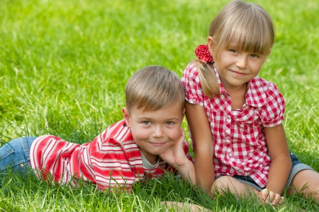 A boy and a girl are resting on the green grass in summer photo