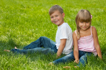 A laughing boy and a smiling girl are sitting together on the grass photo