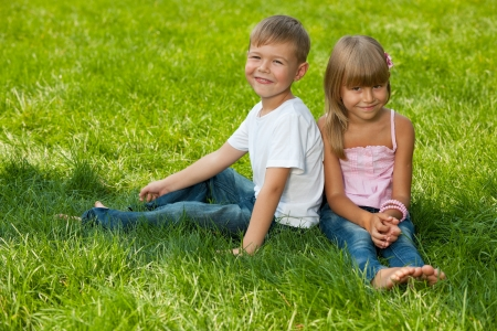A handsome boy and a pretty girl are sitting on the green grass in summer photo