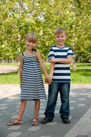 A boy and a girl are standing together in the garden photo