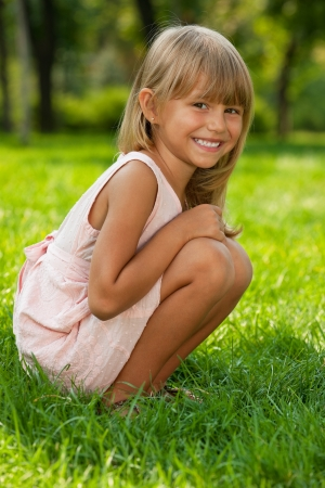 A pretty little girl sits on the green grass in the park photo
