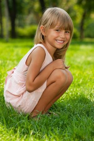 ni�a: Una ni�a bonita se sienta en la hierba verde en el parque