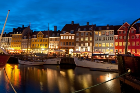 unrecognizable people: Copenhagen, Denmark - June 1, 2012: Boats at the harbor in Nyhavn at night against cafes with unrecognizable people. Nyhavn is a 17th century embankment, canal and entertainment area in Copenhagen. GPS information is in the file