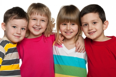 Four laughing kids are standing together; isolated on the white background Standard-Bild