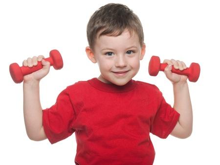 levantando pesas: Muchacho sonriente que hace ejercicios con pesas, aislado en el fondo blanco Foto de archivo