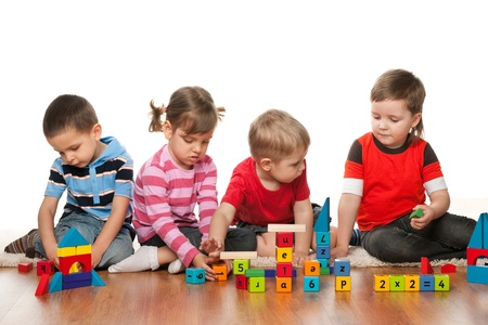 wooden toy: Four children are playing on the floor with blocks Stock Photo