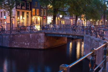 made in netherlands: Amsterdam, Netherlands - May 27, 2012: Bicycles on the bridge over an Amsterdam canal at night. More than 60% of trips in the center of Amsterdam are made by bike. GPS information is in the file.