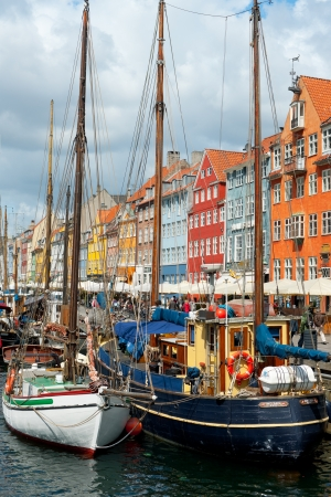 copenhagen: Copenhagen, Denmark - June 1, 2012: Boats at the harbor in Nyhavn against multicolored houses. Nyhavn is a 17th century embankment, canal and entertainment area in Copenhagen. GPS information is in the file