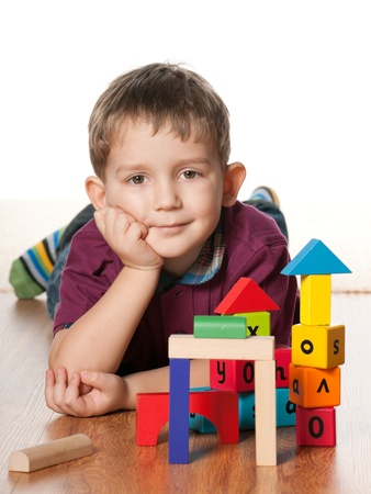 only boys: A little boy is lying on the floor near toys; on the white background Stock Photo