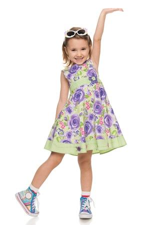 jolie petite fille: Un portrait d'une jeune fille gaie peu fait un geste de la main; isolé sur le fond blanc Banque d'images