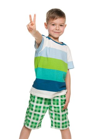 A portrait of a cheerful little boy shows victory sign; isolated on the white background photo