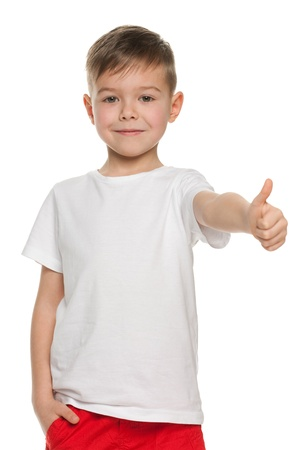 A smiling little boy holding his thumb up; isolated on the white background