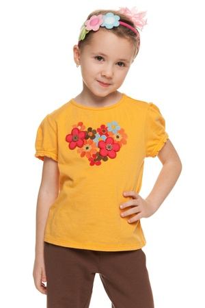 yellow shirt: A portrait of a pensive little girl in yellow shirt; isolated on the white background
