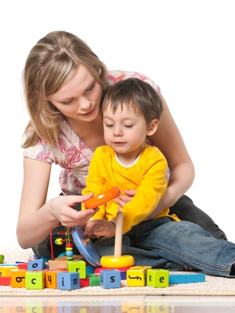 Mother and son playing on the floor with toys; on the white background
