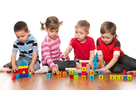 plaything: Four kids are playing on the floor with blocks