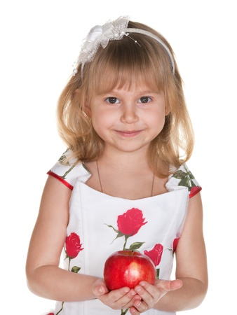A cheerful little girl dressed in a ball gown is holding a red apple photo
