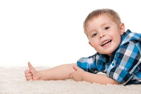 pulgar levantado: Un muchacho sonriente est� mintiendo en la alfombra blanca y sosteniendo el pulgar para arriba Foto de archivo