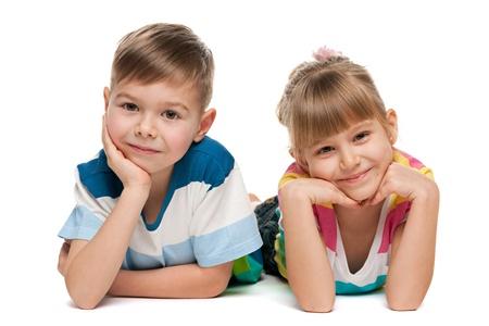 niño y niña: Chico alegre y una chica están mintiendo juntos en el fondo blanco Foto de archivo