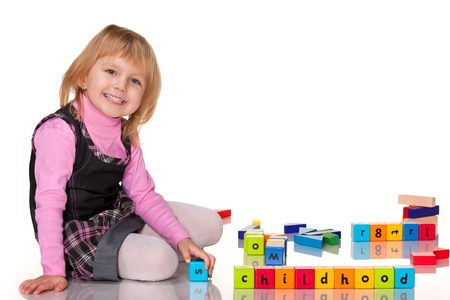 A smiling little girl is playing on the floor photo
