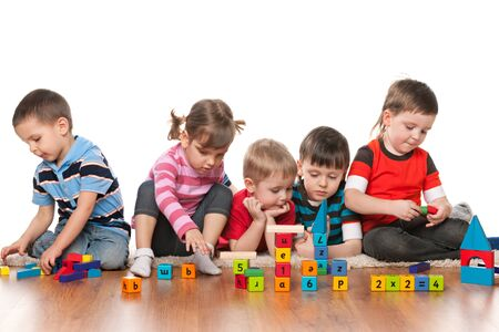 plaything: Five kids are playing on the floor with blocks in kindergarten