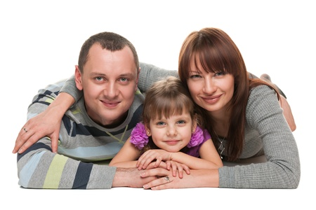 Mother, father and a daughter are lying on the white background photo