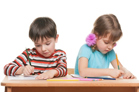 working class: Two children are sitting at the desk and write Stock Photo