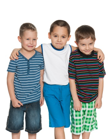 Three little boys are standing together on the white background photo