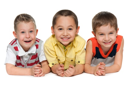 Three little laughing boys lie together on the white background photo