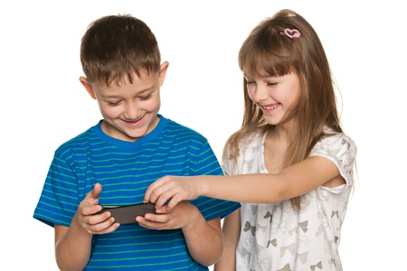 Two children are playing with smartphone on the white background