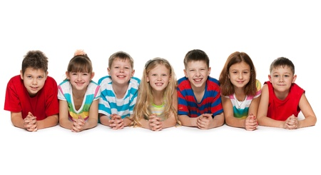 diversity children: Seven children are lying on the floor on a white background Stock Photo