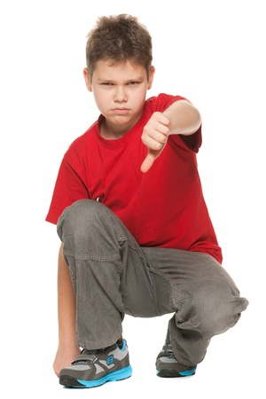 An upset boy in red shirt holding his thumb down on the white background photo