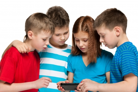 diversity children: Group of four children are playing with smartphone on the white background