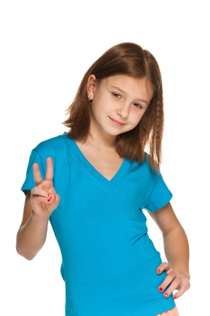 A portrait of a pretty girl in a blue blouse makes a victory sign photo