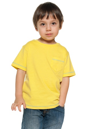 Serious little boy in yellow shirt on the white background Stock Photo