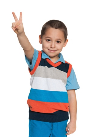 A portrait of a cheerful little boy shows victory sign on the white background photo