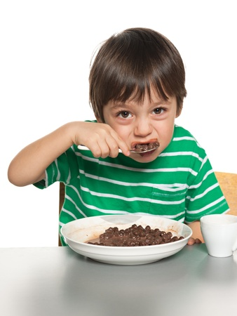 A little boy eats with a spoon his breakfast; on the white background photo