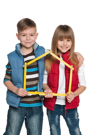 Two cheerful children are holding model of a house photo
