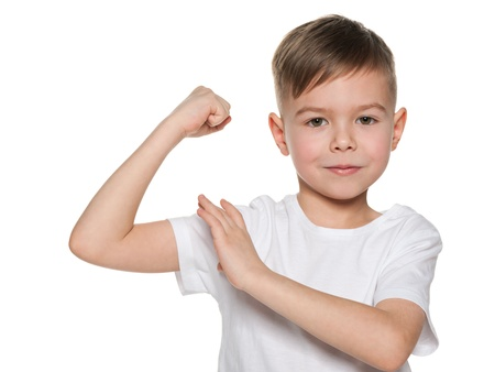boy muscles: A smiling boy is showing the results of his morning exercises
