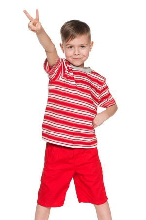 A portrait of a cheerful little boy in red shows victory sign; on the white background photo