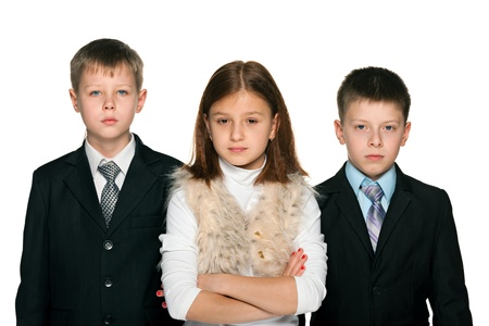 two boys: Pretty young girl is standing with two serious yong boys; on the white background Stock Photo