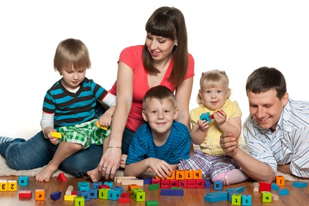 A mother, father, two sons and a daughter are playing on the floor with blocks photo
