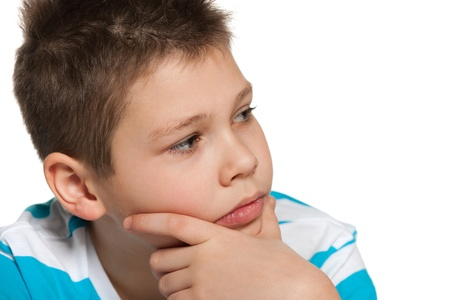 aside: A portrait of a thoughtful boy looking aside; on the white background