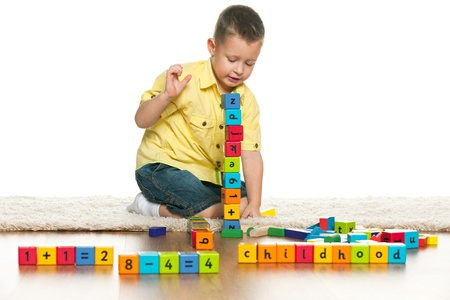 A clever preschool boy is playing with toys on the floor photo