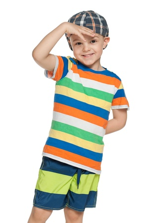 A fashion little boy in cap looks forward; on the white background photo