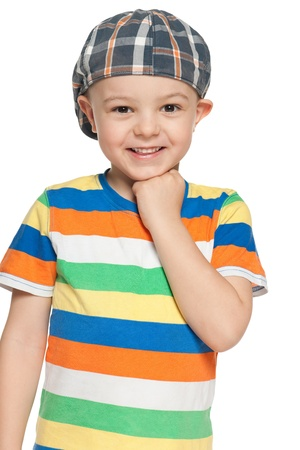 A cheerful little boy in cap looks forward; on the white background photo