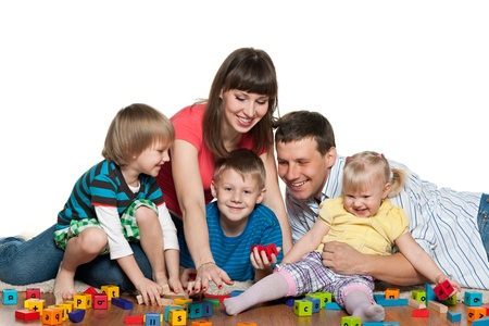 boys toys: Mother, father, two sons and a daughter are playing together on the floor