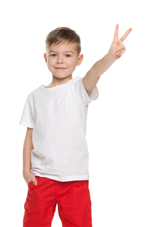A portrait of a cheerful young boy shows victory sign on the white background photo