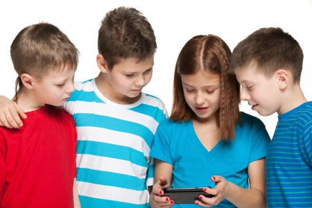Group of four children are playing with a new gadget on the white background photo